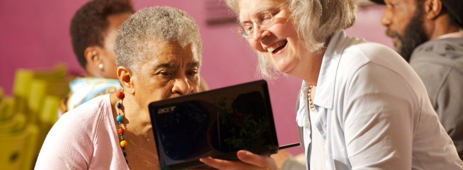 Women at Age UK meeting checking out tablet PC
